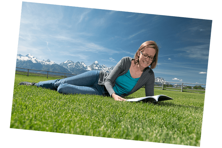 Woman lying in grass reading with Grand Tetons in the background